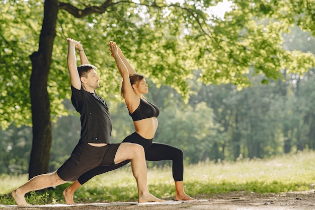 ヨガのフィットネスを行う陽気なカップル。夏の公園の人々。