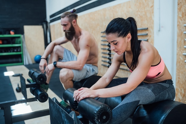 Young sportive couple exhausted indoor gym taking a break