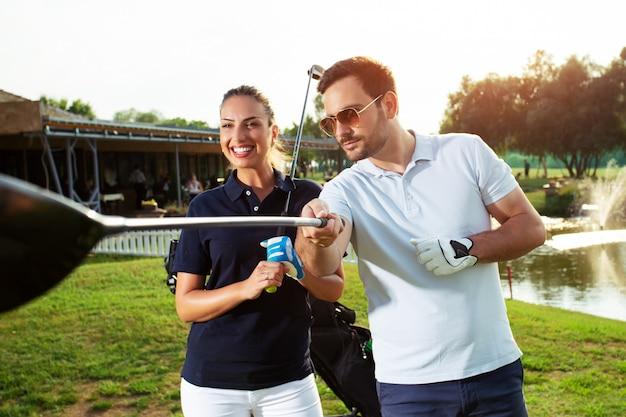 Молодые спортивные пары, играя в гольф на поле для гольфа.