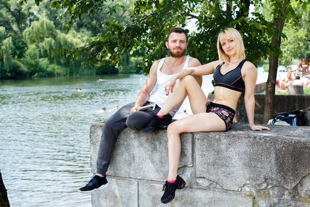 Young sportive couple sitting on a park near a river. man holding white tablet pc