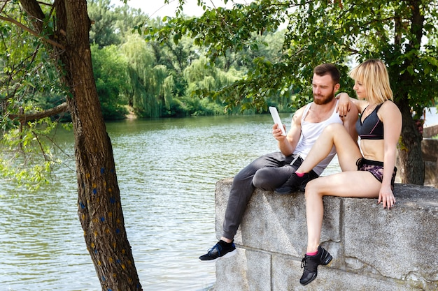 Young sportive couple sitting on a park near a river, use internet on white tablet pc