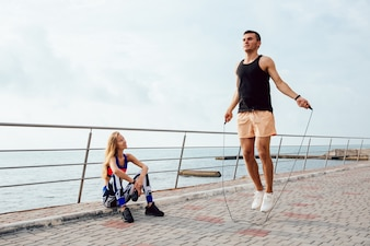 Young sportive couple working out together on the quay, near the sea.