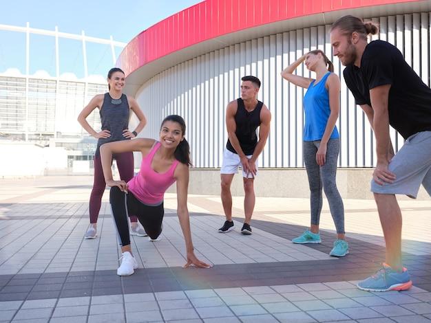 舗装された街の広場でトレーニングをしている若いスポーツの友人