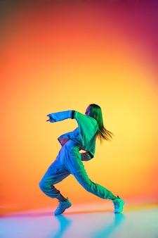 ネオンの光のダンスホールでカラフルな背景にスタイリッシュな服を着てヒップホップを踊る若いスポーティーな女の子。若者文化、動き、スタイルとファッション、アクション。