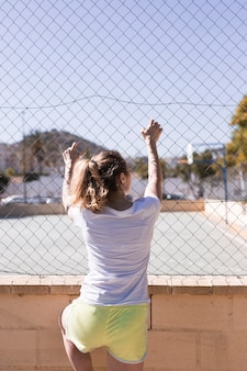 Young sportive girl holding onto metal fence
