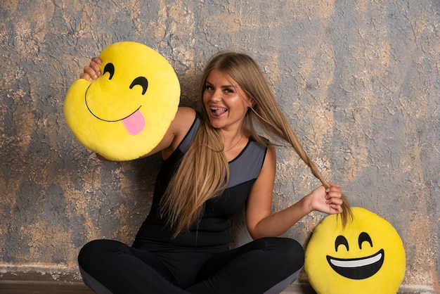Молодая спортивная девушка в спортивной одежде, улыбаясь и высовывая язык из подушек смайликов, веселится.