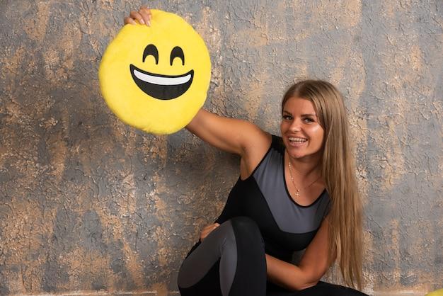 위의 웃는 이모티콘 베개를 들고 스포츠 복장에 낚시를 좋아하는 소녀.