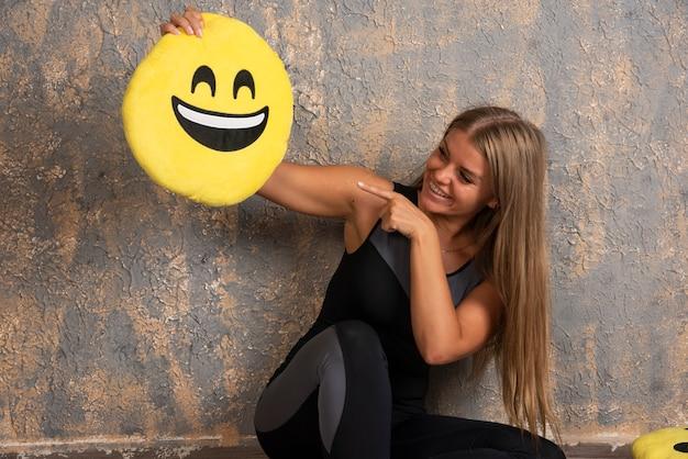웃는 emoji 베개를 들고 그것을 가리키는 스포츠 복장에 낚시를 좋아하는 소녀.