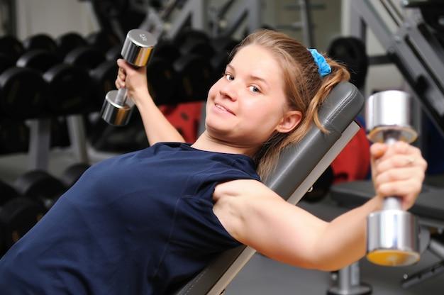 Молодая спортивная девушка в спортивной одежде, лежа на фитнес-оборудовании, тренируется с гантелями в тренажерном зале