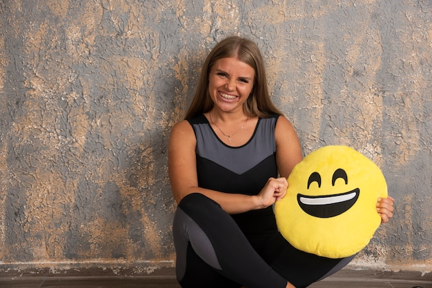 Young sportive girl in sport outfits holding a smiling emoji pillow below.