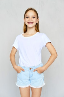 Young sportive girl in t-shirt and jeans shorts posing in studio