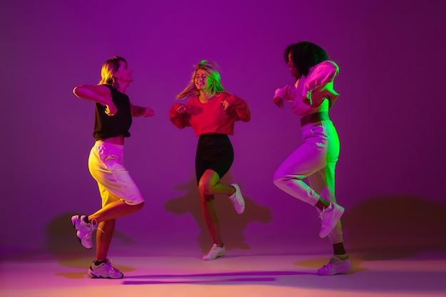녹색 네온 불빛으로 댄스 홀에서 보라색 분홍색 배경에 세련된 옷을 입고 힙합을 춤을 추는 어린 소녀들. 청소년 문화, 운동, 스타일 및 패션, 행동의 개념.