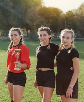 Молодые спортивные девушки позируют с трофеем