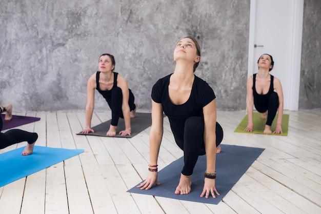スタジオでヨガの練習を練習している女性の若いスポーツグループ