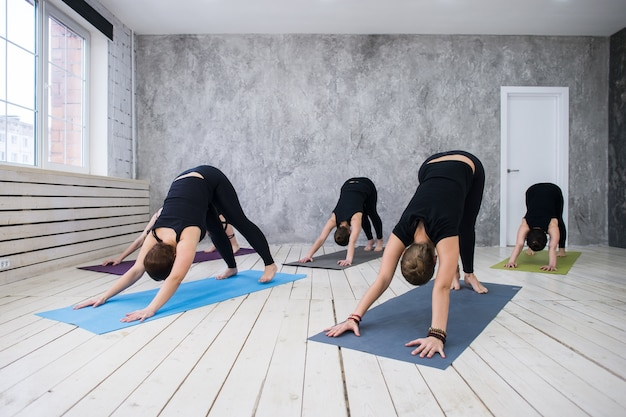 Young sportive group of women practicing yoga exercises in the studio