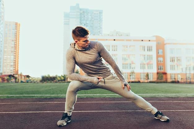 スタジアムで朝のトレーニングで若い陽気な男。彼は灰色のスポーツスーツを着ています。彼はストレッチをしています。