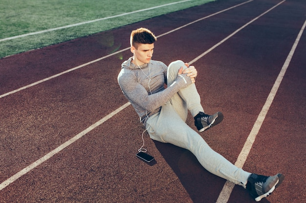 スタジアムで朝のトラックでのトレーニングで若い陽気な男。彼は灰色のスポーツスーツを着ています。上からの眺め。