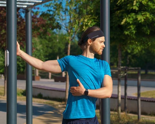 Молодой спортивный красавец делает скручивания туловища во время тренировки на стадионе