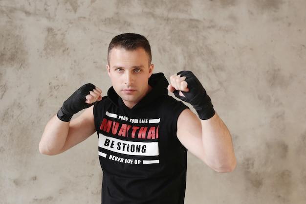 Giovane uomo sportivo che fa karate o trucchi di boxe