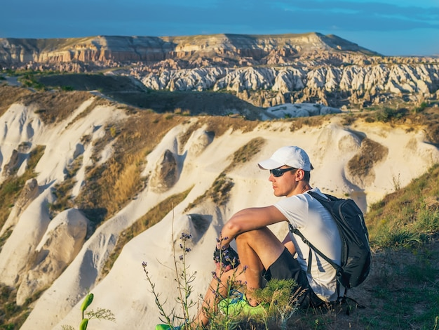 砂岩の岩の頂上に座っているバックパックと白い帽子の陽気な若者