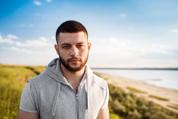 Young sportive man posing in field at sunrise.