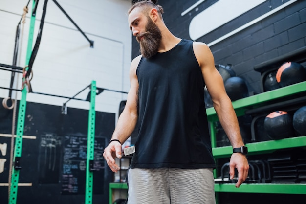 Young sportive man standing indoor gym