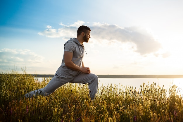 Young sportive man training in field at sunrise.