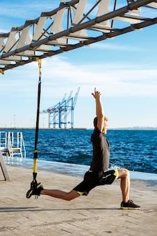 Молодой спортивный человек тренируется с trx возле моря утром
