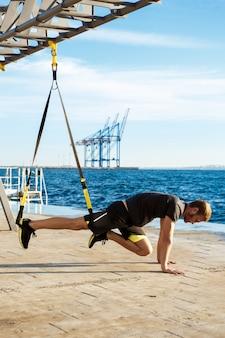 Тренировка молодого спортивного человека с trx около моря в утре.
