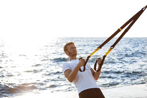Young sportive man training with trx near sea in the morning.