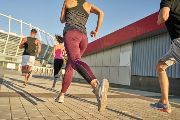 Молодые спортивные люди бегут по асфальтированной дороге