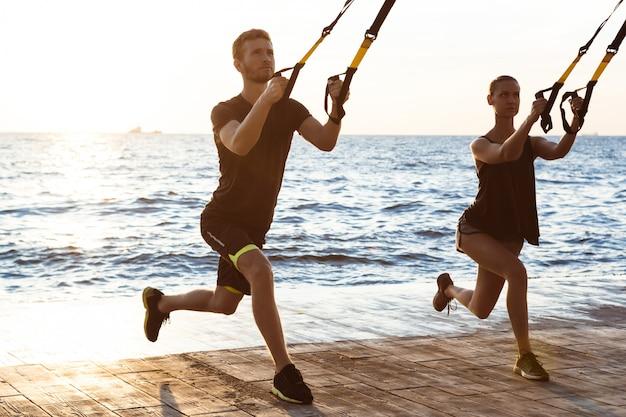 Молодые спортивные люди, обучение с trx возле моря в первой половине дня.