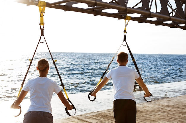 Man and woman doing TRX rollout