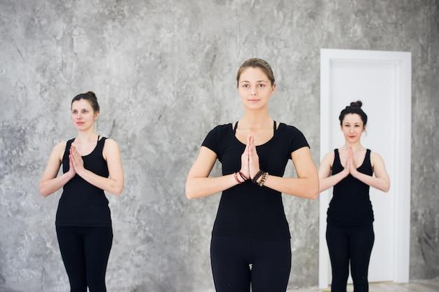 スタジオでヨガの練習を練習している女性の若いスポーツトリオグループ