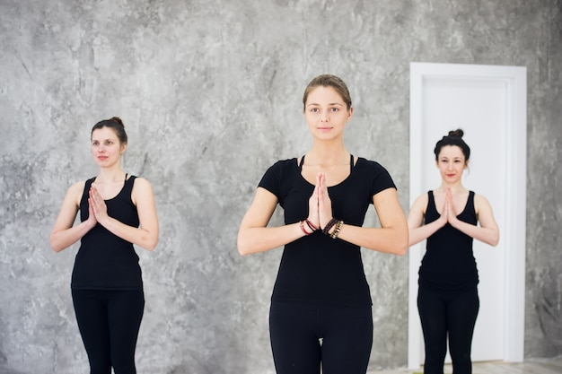 Young sportive trio group of women practicing yoga exercises in the studio