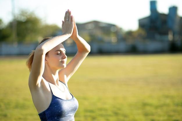 屋外で暖かい夏の日にヨガフィットネスエクササイズをしている若いスポーティーな女性。