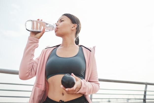 屋外でスポーツトレーニングをした後、ボトルから水を飲む若いスポーツ女性