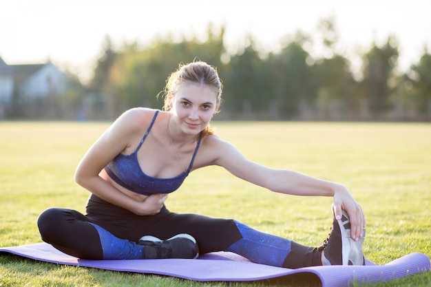 Young sportive woman exercising in morning field outdoors.
