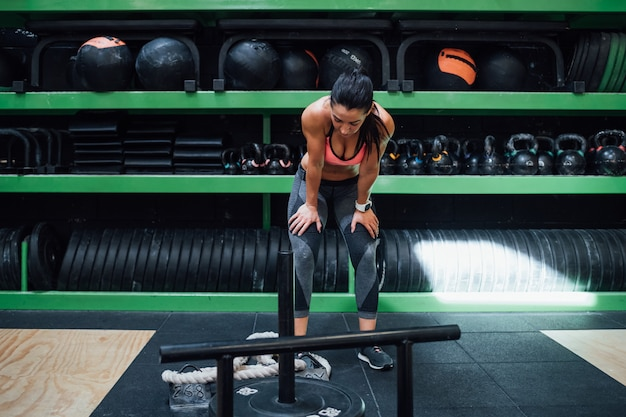 Young sportive woman exhausted indoor gym taking a break