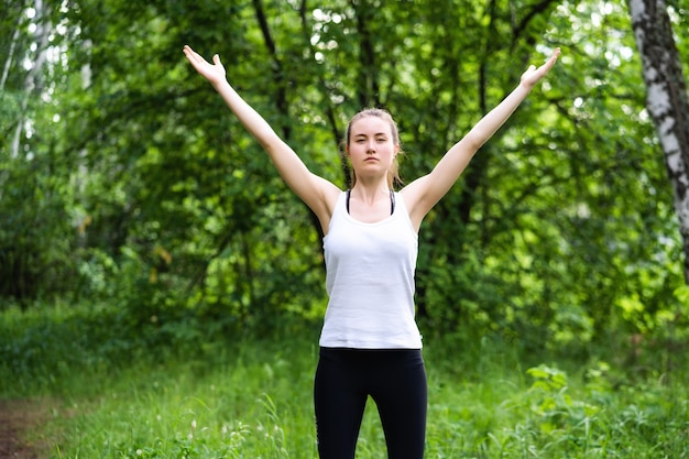 Young sportive woman goes in for sports outdoors. the sportswoman does exercises and warm-ups in the forest against the background of green trees. the concept of a healthy lifestyle and a fit body.