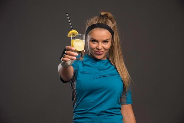 エクササイズ後にレモンとエネルギードリンクを持つ若い陽気な女性
