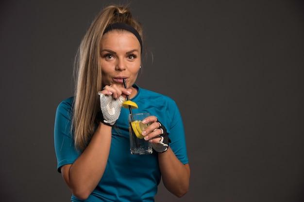 パイプでエナジードリンクを飲んでいる若い陽気な女性。