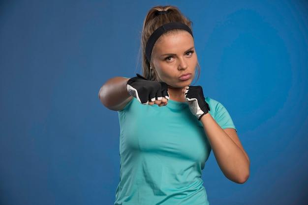 拳とボクシングを保持している若いスポーティーな女性。