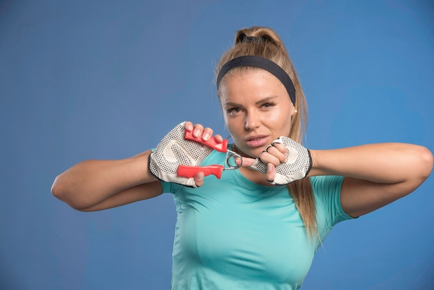 Young sportive woman holding a hand stretching gum and looks tired.