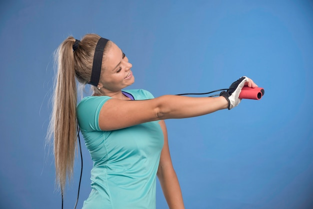 Молодая спортивная женщина держит скакалки и протягивает плечо.