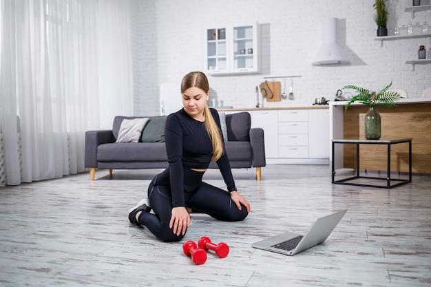 Молодая спортивная женщина в фитнес-одежде в современном доме, используя онлайн-уроки с фитнес-сайта в ноутбуке и тренируясь дома. спорт дома во время карантина