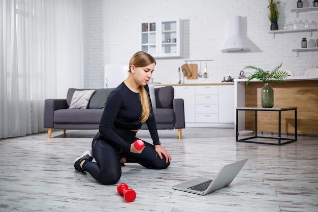 ノートパソコンのフィットネスサイトからのオンラインレッスンを使用し、自宅でトレーニングを行っている現代の家でフィットネス服を着た若いスポーツ女性。検疫中の自宅でのスポーツ