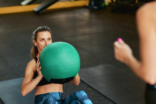 운동복을 입은 젊은 낚시를 좋아하는 여성이 체육관에서 피트니스 공을 가지고 운동하는 복근 운동을 하고 있습니다.