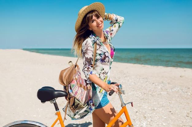 Молодая спортивная женщина в стильном белом топе и джинсовых шортах стоит на пляже с оранжевым велосипедом