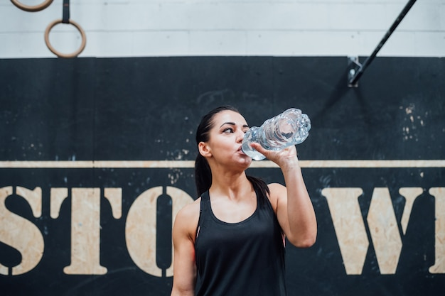 Young sportive woman indoor gym recovering drinking water